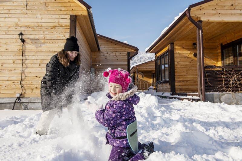 愉快的母亲和的女儿,活跃戏剧在他的多雪的围场 免版税库存图片