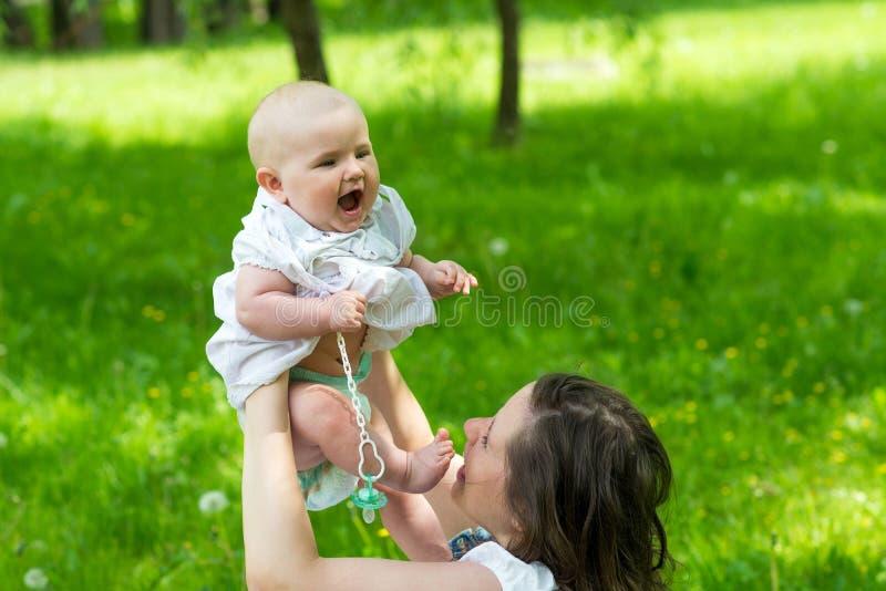 愉快的母亲和逗人喜爱女婴使用室外 库存图片