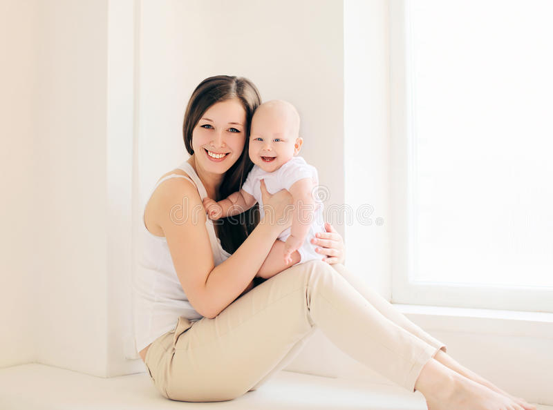 愉快的母亲和婴孩在家 库存图片