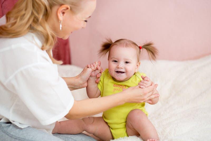 愉快的母亲和婴孩有乐趣消遣 免版税库存图片