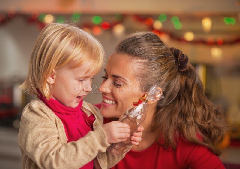 愉快的母亲和婴孩画象用巧克力圣诞老人 图库摄影