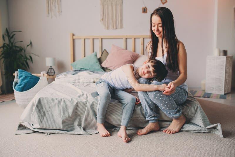 愉快的母亲在早晨拥抱她的小孩儿子,在家坐床 免版税库存图片