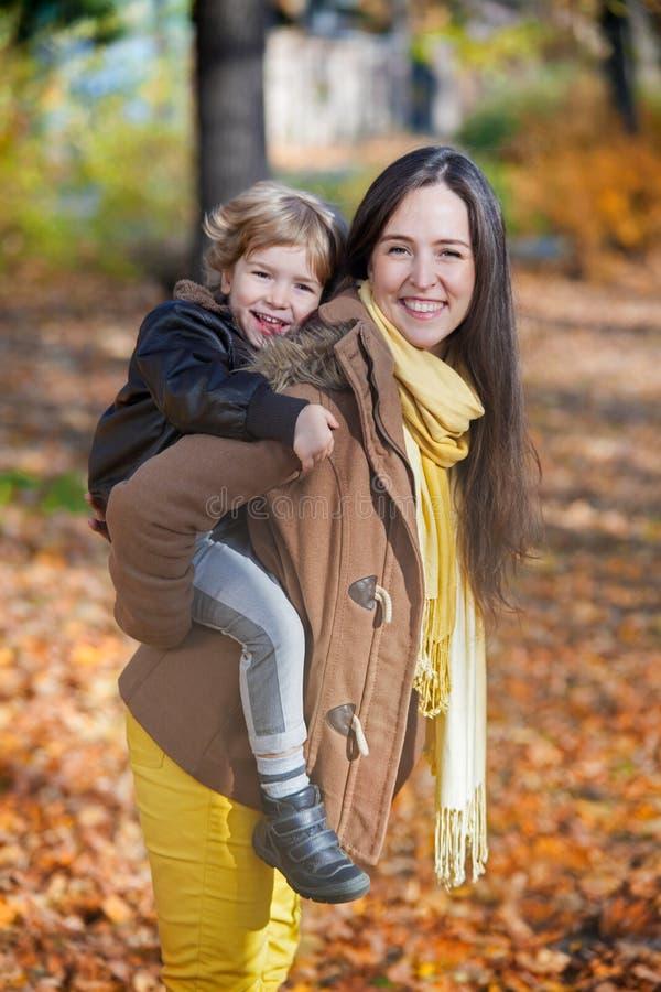 愉快的母亲在秋天的扛在肩上她的儿子 免版税库存图片