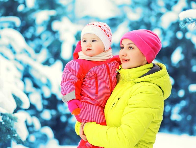 愉快的母亲抱着婴孩的冬天画象移交多雪的圣诞树 免版税库存图片