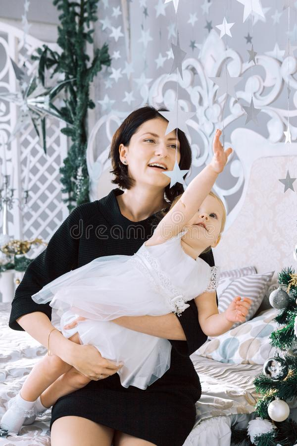 愉快的母亲拿着她的女儿小女孩给礼物和白色兔宝宝的膝部在白色经典内部的圣诞树附近 库存照片