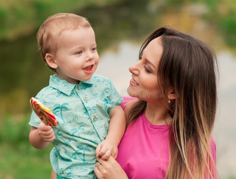 愉快的母亲拿着逗人喜爱的微笑的儿子 库存照片