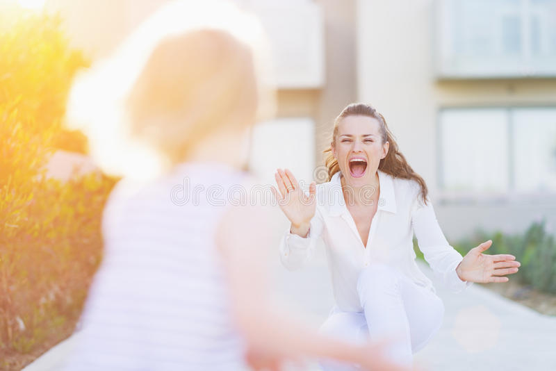 愉快的母亲捉住的跑到她的婴孩 图库摄影