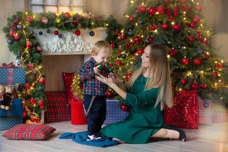 愉快的母亲画象和可爱的婴孩庆祝圣诞节 新年` s假日 有妈妈的小孩的欢乐地装饰 免版税库存图片
