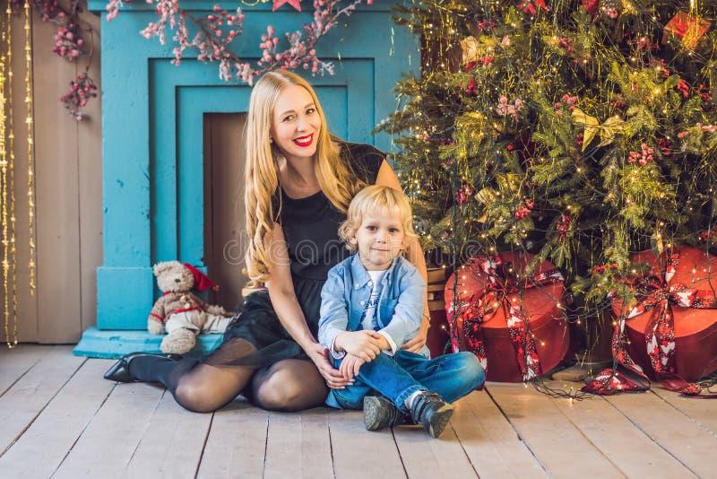 愉快的母亲画象和可爱的男孩庆祝圣诞节 新年` s假日 有妈妈的小孩欢乐地装饰的r的 免版税库存图片