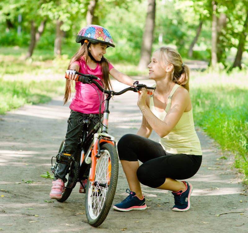 愉快的母亲谈话与微笑她的†‹â€ ‹的女儿,教的骑自行车 免版税库存照片