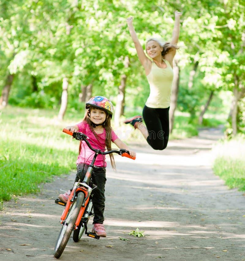 愉快的母亲高兴她的女儿学会骑自行车 库存图片