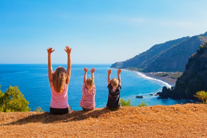 愉快的母亲,在小山的孩子有海峭壁风景视图 免版税图库摄影