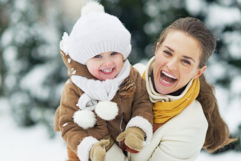 愉快的母亲画象和婴孩在冬天停放 免版税图库摄影