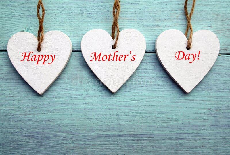 愉快的母亲` s天概念 在蓝色土气木背景的装饰白色木心脏 库存照片