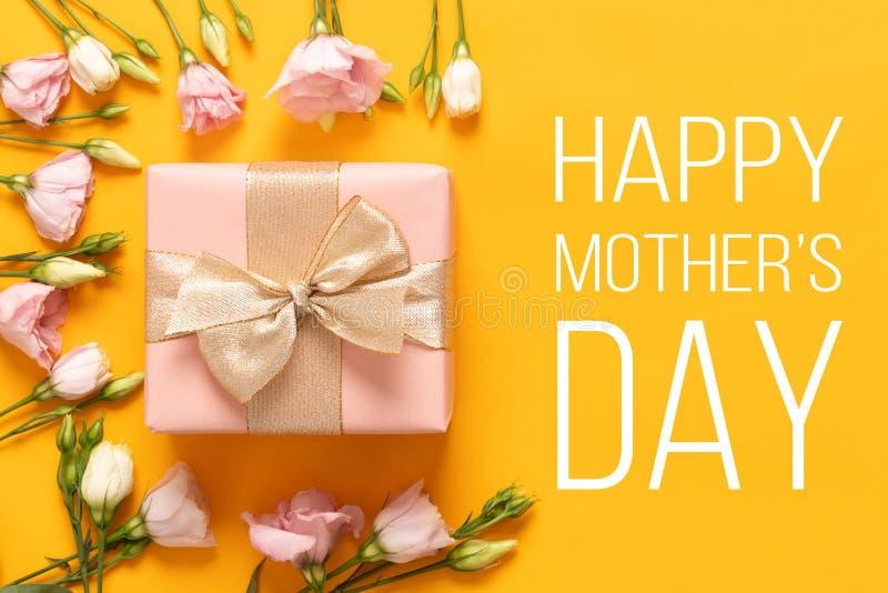 愉快的母亲` s日背景 明亮的黄色和粉红彩笔色的母亲节背景 舱内甲板与礼物盒的被放置的贺卡 库存图片