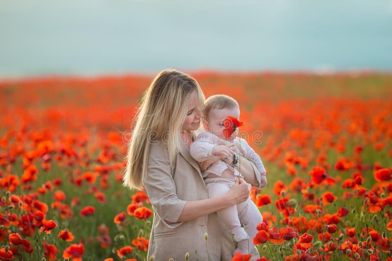 愉快的母性 妈妈和儿子女儿在使用开花领域红色鸦片 库存照片