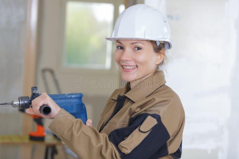 愉快的母承包商钻墙壁在建造场所 图库摄影