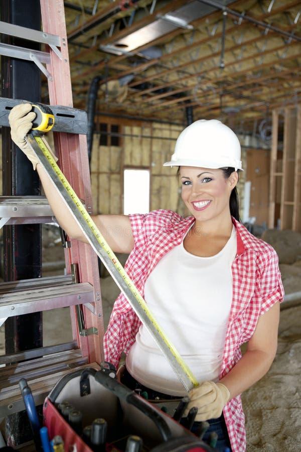 愉快的母承包商画象与测量的磁带的在建造场所 免版税库存图片