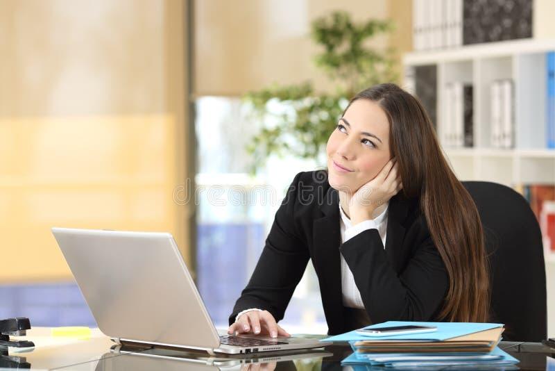 愉快的沉思女实业家在办公室 免版税库存照片