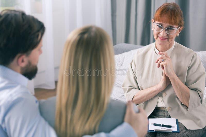 愉快的治疗师感到骄傲为她的患者 库存图片