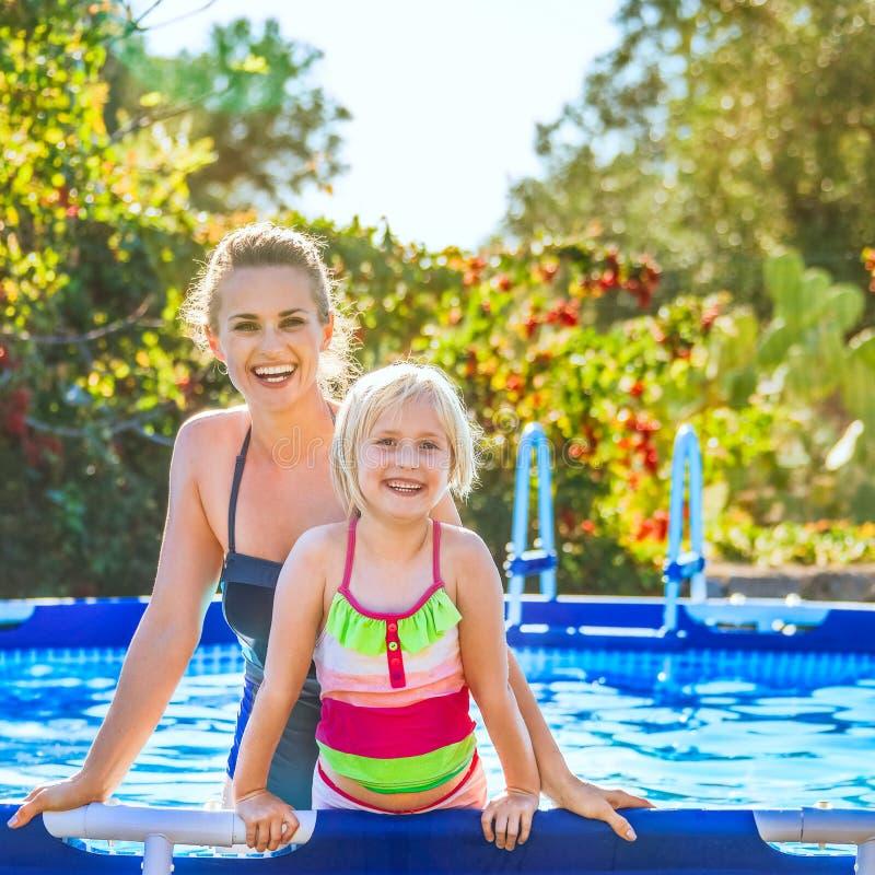愉快的活跃站立在游泳池的母亲和女儿 免版税库存照片