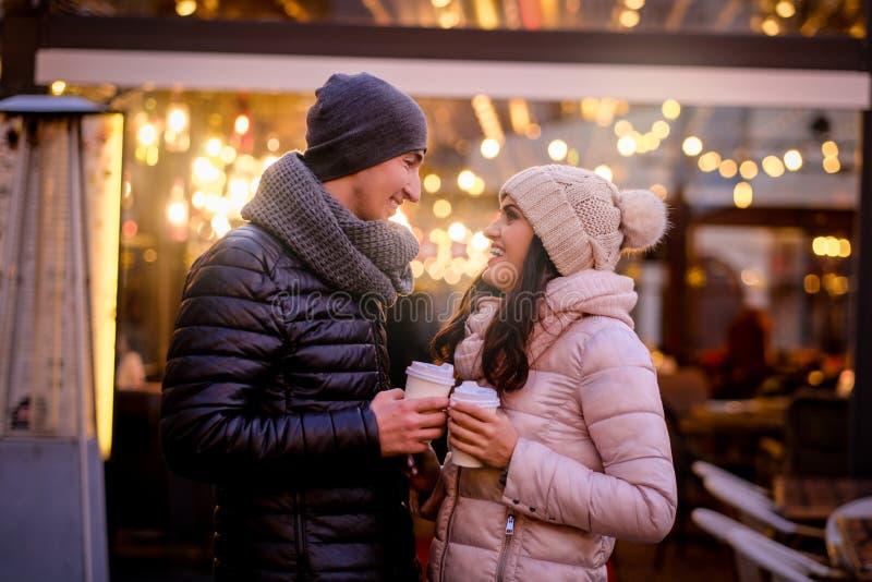 愉快的浪漫享用夫妇佩带的衣服暖和一起花费时间在平衡街道的一个日期上在咖啡馆附近 免版税库存图片