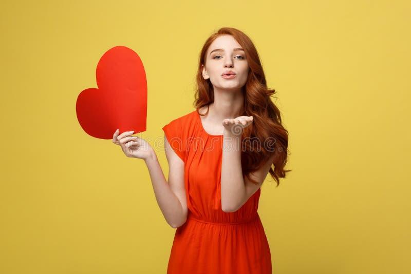 愉快的浪漫年轻白种人女孩画象有红色纸心形的明信片的,浪漫愿望,情人节 免版税库存图片