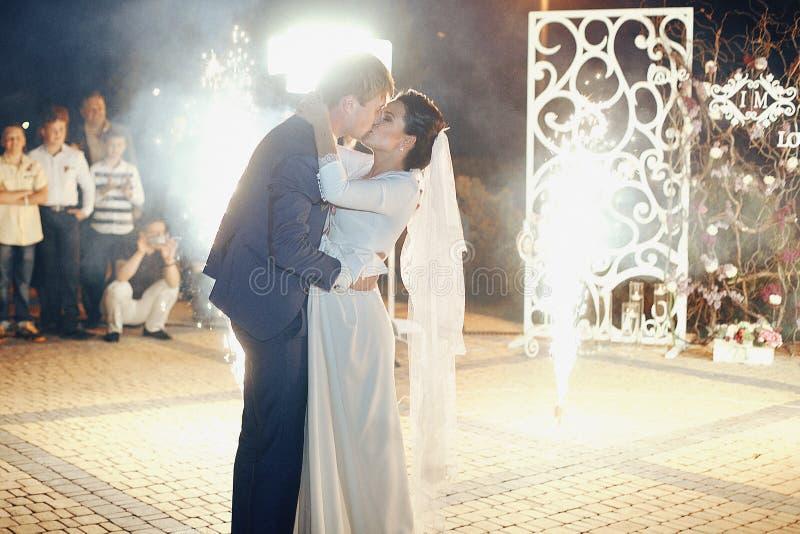愉快的浪漫新婚佳偶夫妇亲吻在招待会的,烟花b 免版税库存图片