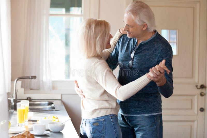 愉快的浪漫资深夫妇舞蹈在烹调食物的厨房里 免版税库存图片