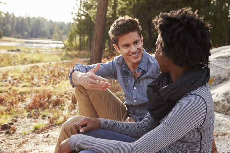 愉快的混合的族种夫妇谈话在乡下 免版税库存照片