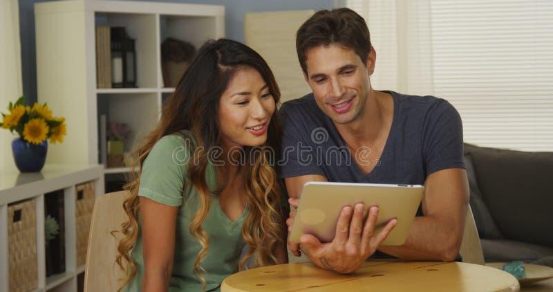 愉快的混合的族种夫妇谈话在片剂 免版税库存照片