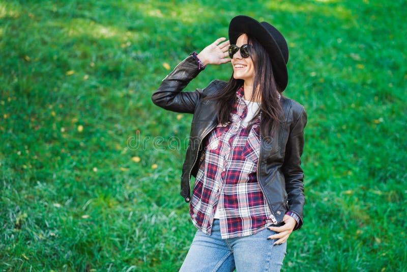 愉快的混合的族种年轻女人画象帽子的 西班牙行家女孩在公园 夫人佩带的格子衬衫和 免版税库存图片