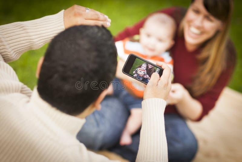 愉快的混合的族种父母和采取自画象的男婴 图库摄影