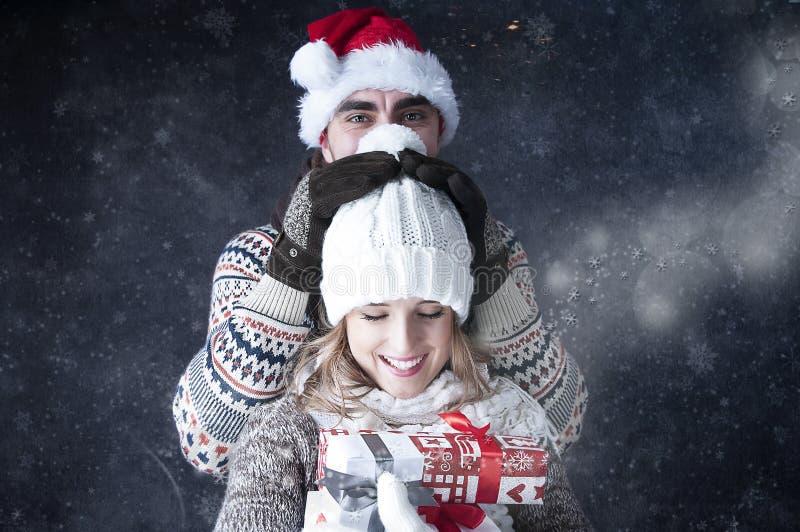 愉快的滑稽的夫妇覆盖物雪背景。 免版税图库摄影