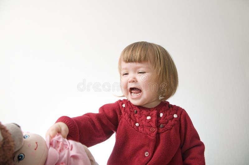 愉快的滑稽的女孩情感使用 有熊和玩偶的逗人喜爱的白种人白肤金发的女婴 免版税库存照片