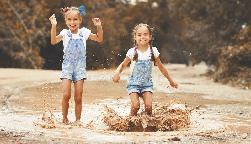 愉快的滑稽的姐妹孪生跳在磨擦的水坑的儿童女孩 库存照片