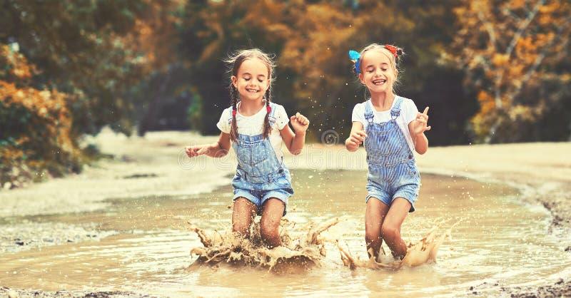 愉快的滑稽的姐妹由跳在水坑和笑的女孩孪生孩子 免版税库存图片