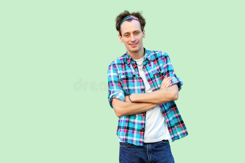 愉快的满意的年轻人画象偶然蓝色方格的衬衣和头饰带身分的,看与croseed胳膊的照相机 库存图片