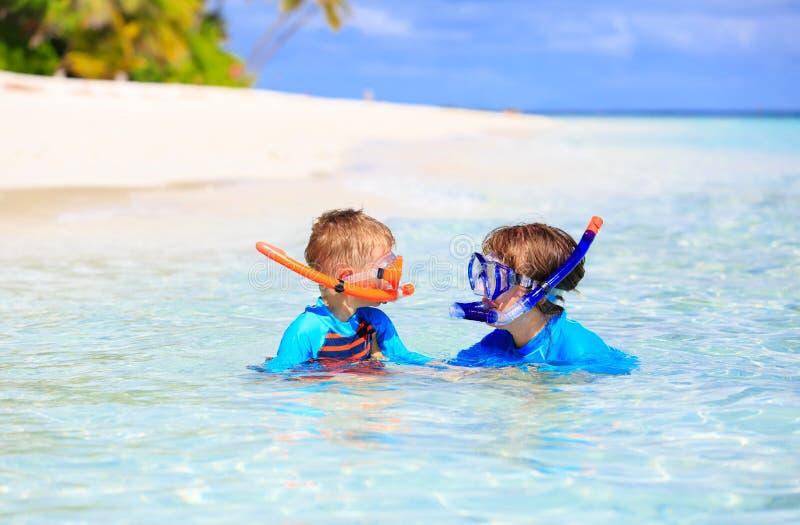 愉快的潜航在海滩的母亲和儿子 免版税库存图片