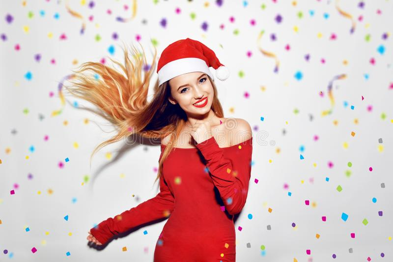 愉快的激动的少妇在圣诞老人帽子跳舞和微笑在白色背景,飞行confitti 红色礼服的, l俏丽的女孩 免版税库存照片