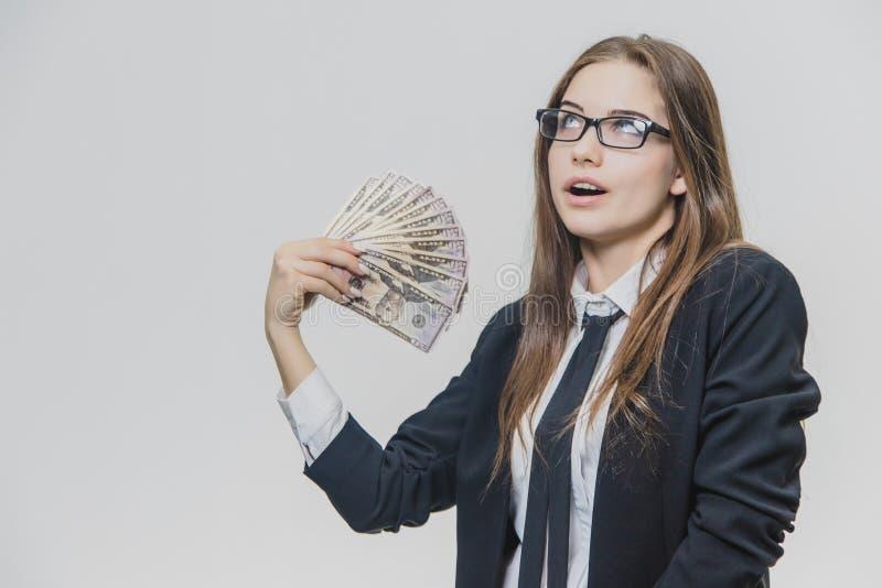 愉快的激动的年轻女商人显示一堆金钱,隔绝在白色背景 女孩由巨大满意 免版税库存照片
