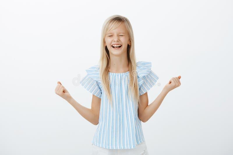 愉快的激动的美丽的女孩画象有公平的头发的在蓝色女衬衫,握紧被举的拳头,闭合值的眼睛和 库存图片