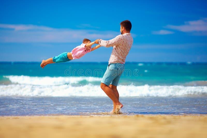 愉快的激动的获得父亲和的儿子在夏天海滩的乐趣,享有生活 免版税库存图片