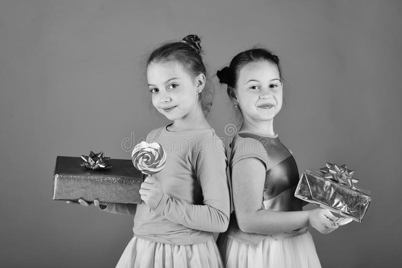 愉快的点心概念 有棒棒糖、箱子和袋子的姐妹 孩子吃五颜六色的焦糖 免版税库存照片