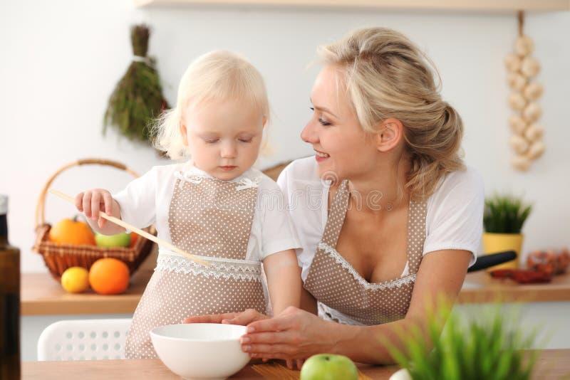 愉快的烹调在厨房里的母亲和小女儿 消费时间全部一起,家庭乐趣概念 免版税库存图片