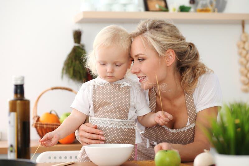 愉快的烹调在厨房里的母亲和小女儿 消费时间全部一起,家庭乐趣概念 免版税图库摄影