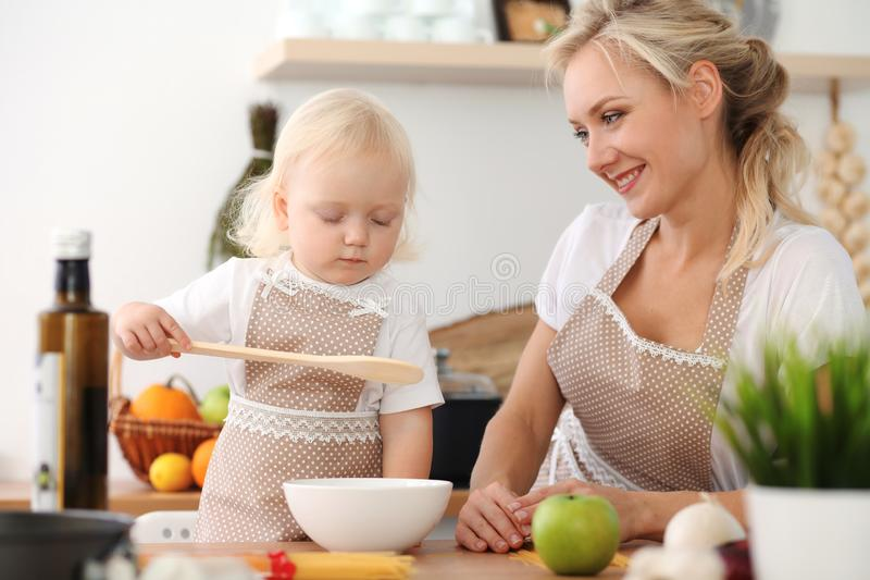 愉快的烹调在厨房里的母亲和小女儿 消费时间全部一起,家庭乐趣概念 库存照片