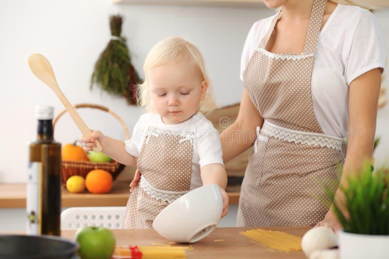 愉快的烹调在厨房里的母亲和小女儿 消费时间全部一起,家庭乐趣概念 库存图片