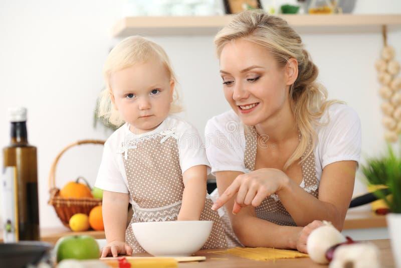 愉快的烹调在厨房里的母亲和小女儿 消费时间全部一起,家庭乐趣概念 图库摄影