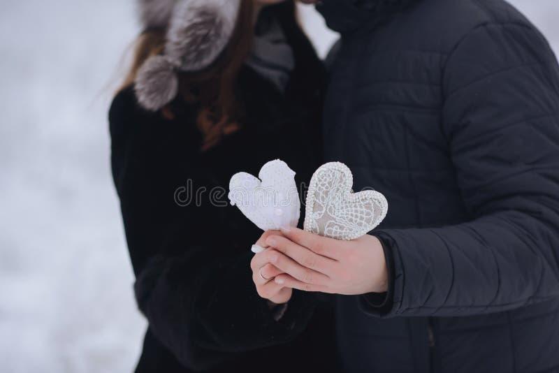 愉快的爱夫妇在森林里在冬天、步行、亲吻、拥抱和举行纸心脏在公园-情人节 免版税库存图片